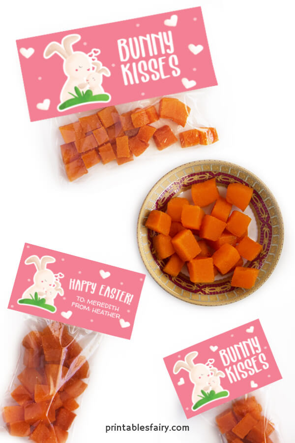 Bags of orange gummies with pink toppers that read happy Easter next to an illustration of bunnies kissing