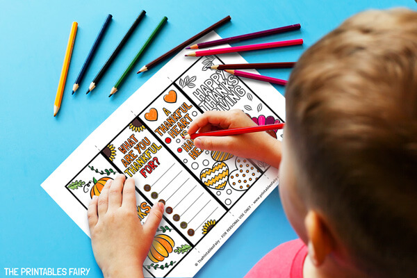 Kid coloring the Thanksgiving bookmarks